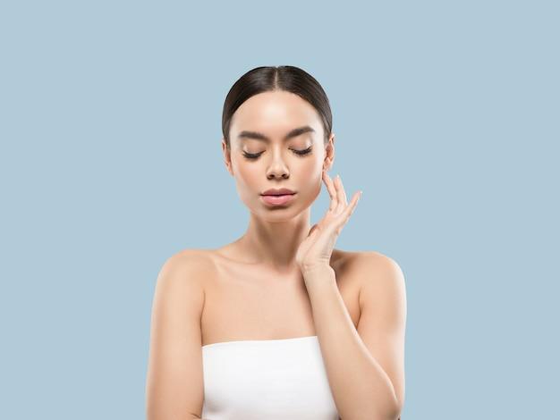 彼女の顔の健康な肌に触れるアジアの女性の美しさの顔の体の肖像画。色の背景。青