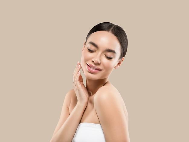 彼女の顔の健康な肌に触れるアジアの女性の美しさの顔の体の肖像画。色の背景。茶色