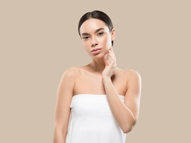 그녀의 얼굴 건강한 피부를 만지고 아시아 여자 아름다움 얼굴 신체 초상화. 색상 배경입니다. 갈색