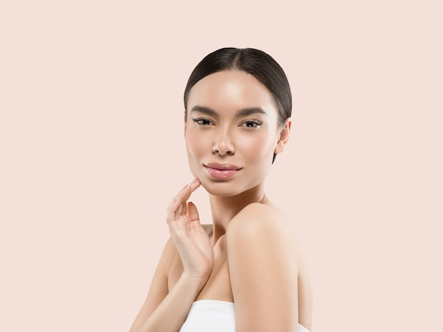 彼女の顔の健康な肌に触れるアジアの女性の美しさの顔の体の肖像画。色の背景。ピンク