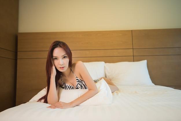 Азиатская женщина бикини позирует на белой кровати