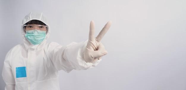 Ppeスーツまたは個人用保護具の制服を着て医療用フェイスマスクを着用しているアジアの女性医師