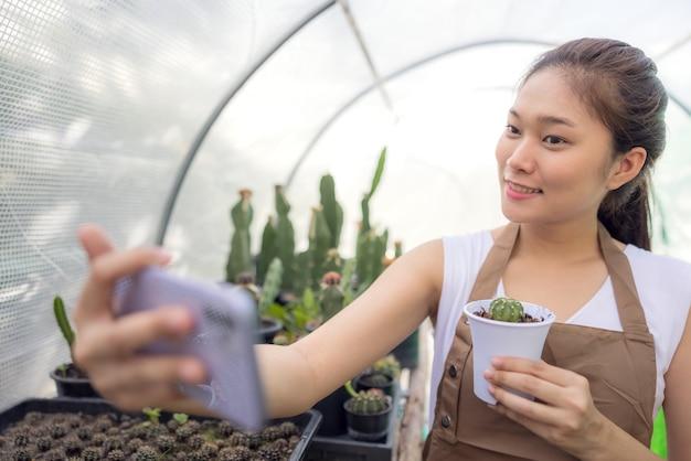 Азиатская женщина увлекается садоводством с кактусами и является владельцем начинающей компании, которая продает деревья через интернет.
