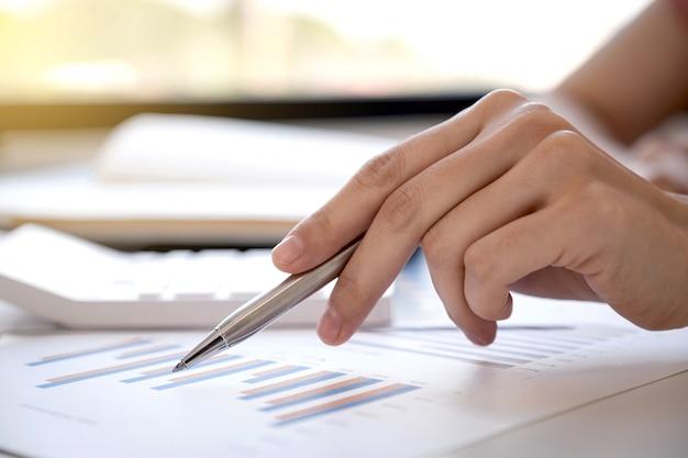 Азиатская женщина рука анализирует пером график с калькулятором и ноутбуком в домашнем офисе
