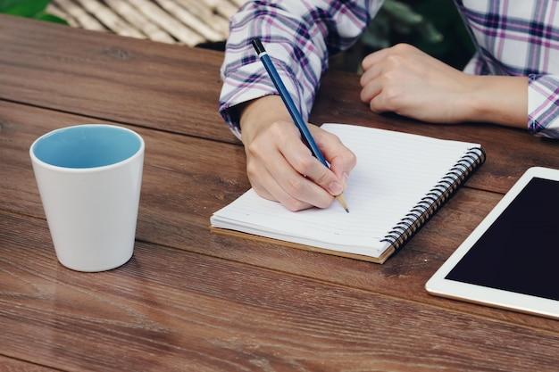 Азия женщина рука, писать ноутбук на деревянный стол в кафе.