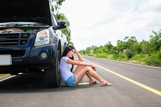 Asia woman have a problem about her car.beautiful lady need someone to help