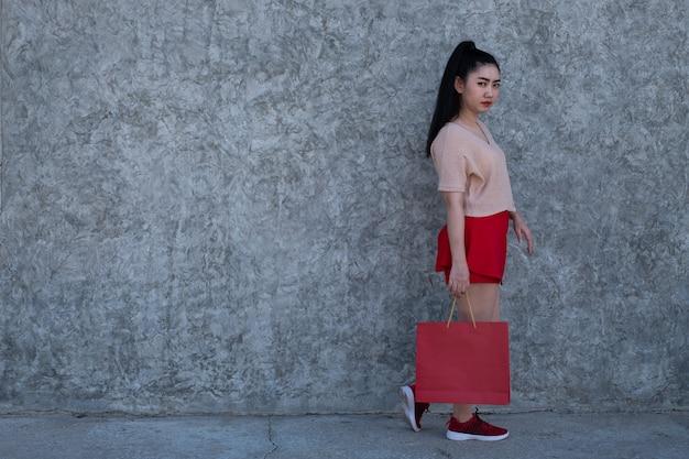 コンクリートの壁の背景で買い物袋を保持しているアジアの女性