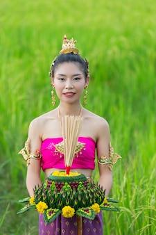 タイのドレスの伝統的なホールドクラトンのアジアの女性。ロイクラトンフェスティバル