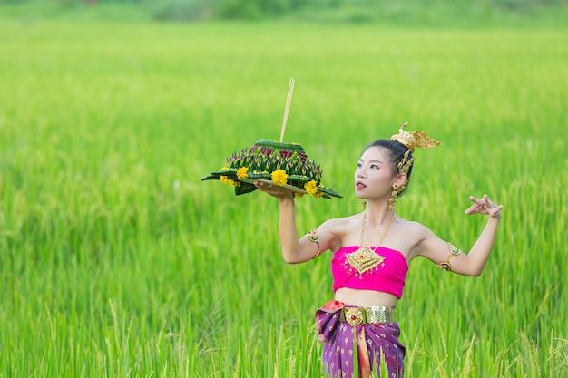 Азиатская женщина в тайском традиционном владении kratong. фестиваль лой кратонг