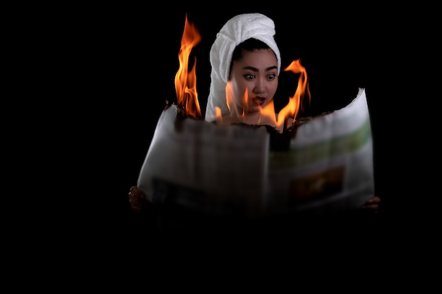 Азиатская женщина держит зажженную и читает горящую огнем газету на черном фоне