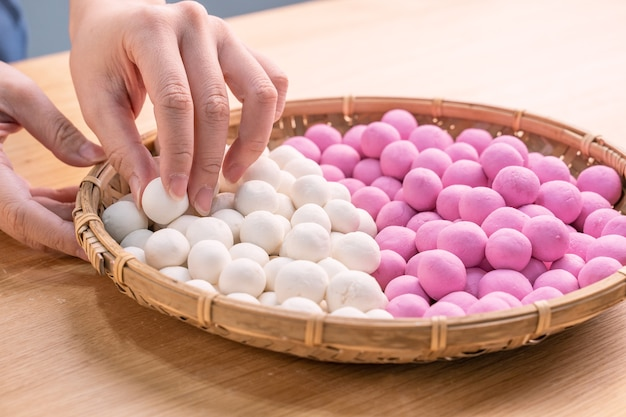 An asia woman is making tang yuan, yuan xiao, chinese traditional food rice dumplings in red and white for lunar new year, winter festival, close up.