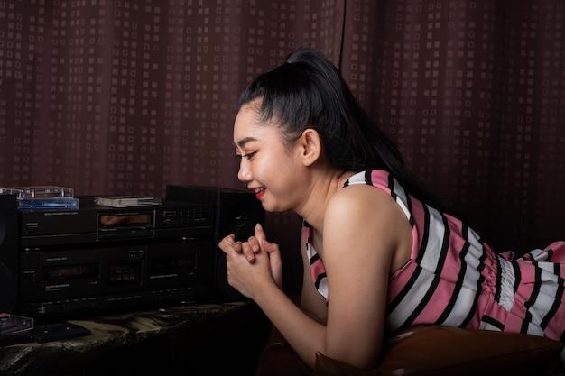 ステレオカセットテーププレーヤーからの音楽を聴いている黒い革張りのソファに腰を下ろすアジアの女性
