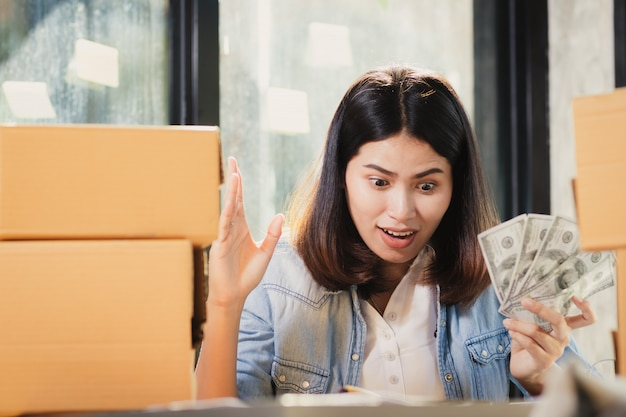 アジアの女性が驚きとお金を見て。