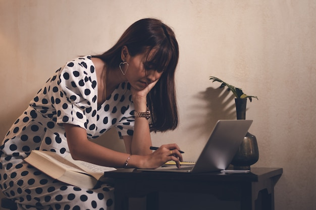 Asia woman reading book  and using laptop,note pad in free time with happy