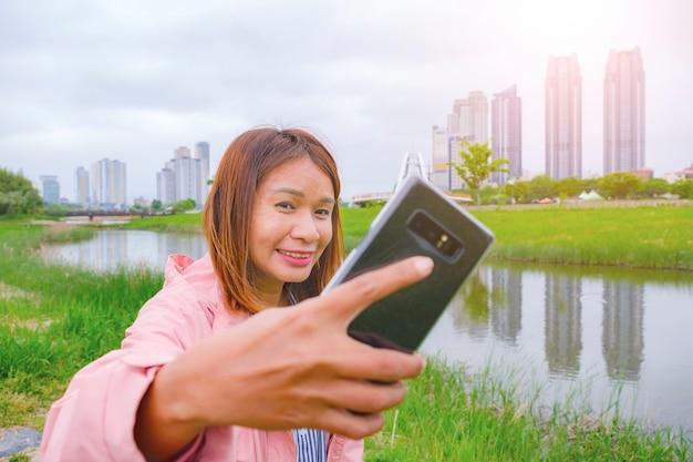 4月に韓国蔚山のテファガングランドパークでスマートフォンを使ったアジアの女性の自撮り写真。
