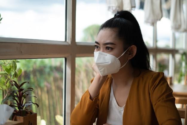 座って医療用マスクを着用しているアジアの女性