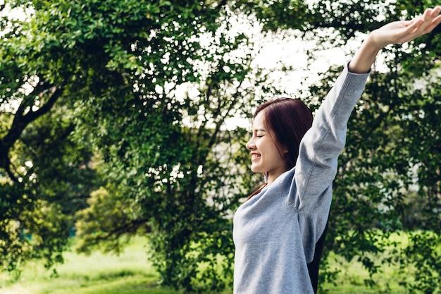 彼女の腕を伸ばして立っているアジアの女性はリラックスして自然の新鮮な空気を楽しむ
