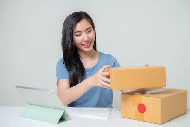 アジアの女性がオンラインでビジネスを始めます。オンラインショッピングの中小企業の起業家またはフリーランスの仕事の概念を持つ人々。バナーサイズ