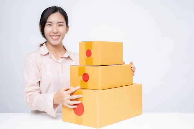 アジアの女性はビジネスオンラインのために起動します。オンラインショッピングの中小企業の起業家またはフリーランスの仕事の概念を持つ人々。