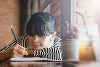 アジアの女の子の十代、ノートパソコンの紙に書く女の子、楽しい、幸せで宿題をする。