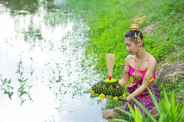 Donna dell'asia nel kratong tradizionale della stretta del vestito tailandese. festival di loy krathong