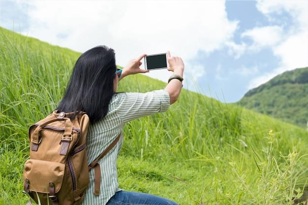 Азия женщина-путешественник с рюкзаком использовать мобильный телефон сфотографировать пейзаж горы