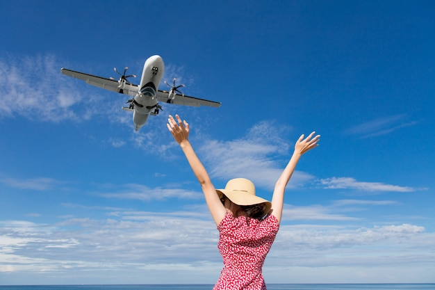 Asia woman traveling looking at the flying plane above the sea