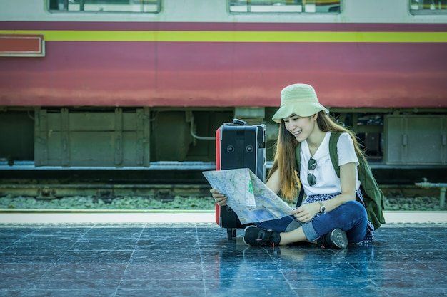 アジアの女性旅行者は列車の駅で旅行に行く前に座って、地図を見て、旅行