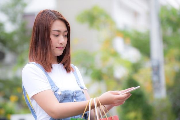通りでスマートフォンを使用してアジアの女性