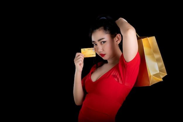 クレジットカードと買い物袋を保持している赤いドレスを着ているアジアの女性