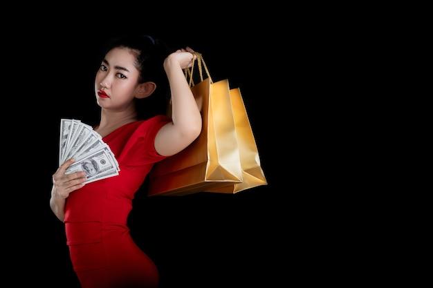 黒の背景の上にクレジットカードと買い物袋を保持している赤いドレスを着ているアジアの女性