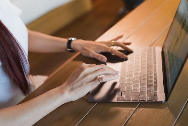 テーブルに座っているラップトップを持つアジアの女性