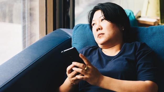 ソファでスマートフォンを考えているアジアの女性40