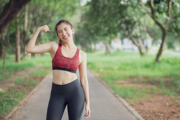 アジアの女性は公園でのトレーニング中に音楽を聴きます。