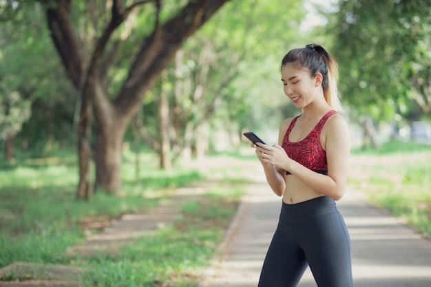 Азиатские женщины слушают музыку во время тренировки в парке.
