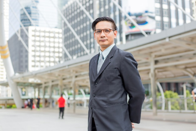 Asia young business man in front of the modern building in downtown .concept of young  business people