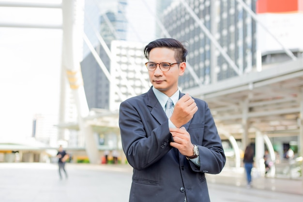 Asia young business man in front of the modern building in downtown