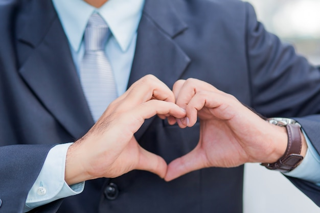 Asia young businessman making a heart with his hands, i love business