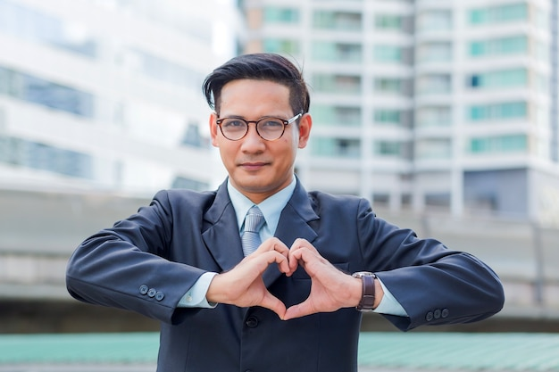 Asia young businessman making a heart with his hands over white background, i love busines