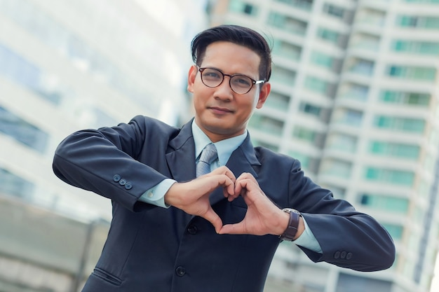 Asia young businessman making a heart with his hands over white background, i love business