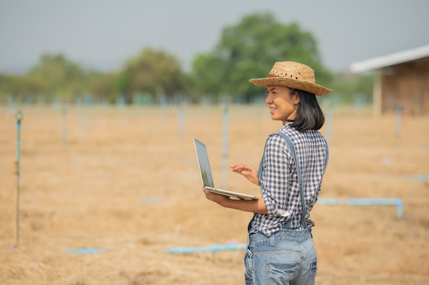 Asia young female farmer in hat standing in field and typing on keyboard of laptop computer. woman with laptop supervising work on farmland,  concept ecology, transport, clean air, food, bio product
