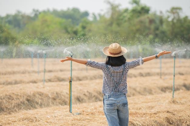 Молодая женщина-фермер азии в шляпе стоя и ходить в поле женщина для проверки в сельскохозяйственном саду. рост растений. понятие экология, транспорт, чистый воздух, еда, биопродукт.