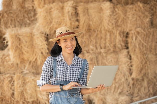 필드에 서 노트북 컴퓨터의 키보드에 입력 모자에 아시아 젊은 여성 농부. 농지, 개념 생태학, 운송, 깨끗한 공기, 음식, 바이오 제품에 대한 작업을 감독하는 노트북을 가진 여자