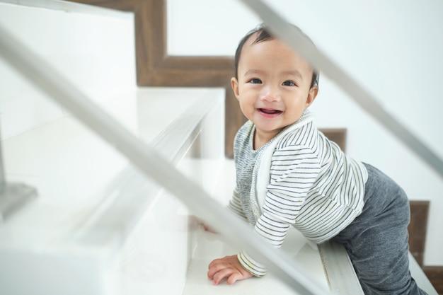 アジアの10ヶ月歳の幼児赤ちゃん女の子子供一人で家で階段を登って、見て、笑っています。動き、バランスと調整、マイルストーンのコンセプト