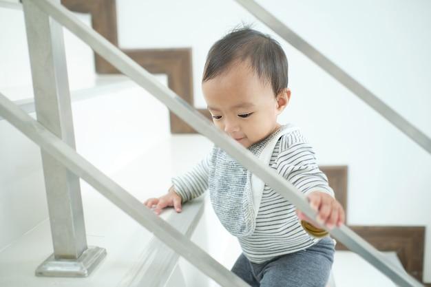 アジアの10か月の幼児の赤ちゃん女の子子供一人で家で階段を上る、運動、階段の発達のマイルストーンの概念を登る