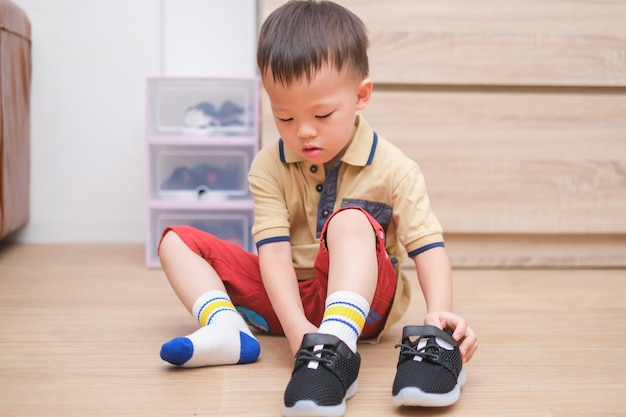 Asian 2 - 3 years old toddler boy sitting and concentrate on putting on his black shoes / sneakers