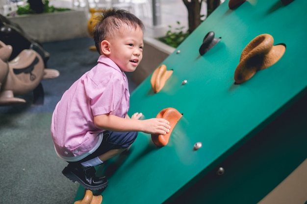 Asian 2 - 3 years old toddler child having fun trying to climb on artificial boulders at schoolyard playground, little boy climbing up rock wall