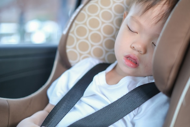 Asian 2 -3 years toddler baby boy child sleeping in modern car seat. child traveling safety on the road