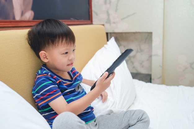 Asian 3 - 4 years old toddler boy child sitting in bed holding the tv remote control and watching television in bedroom at home