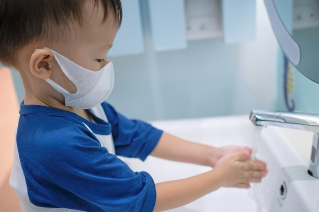 Asian 3 - 4 years old toddler boy child wearing protective medical mask washing hands by himself on sink in public toilet / bathroom for kids - soft & selective focus